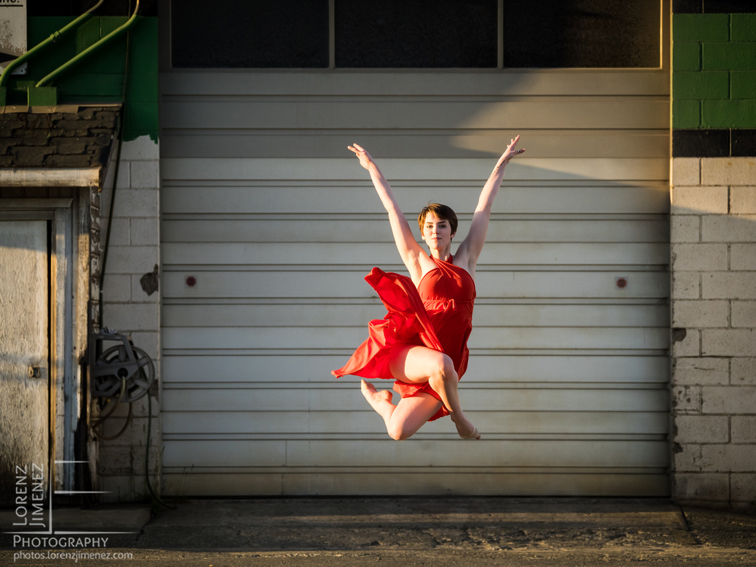 A dancer performs a spinning leap in front of a garage door in an industrial parking lot.